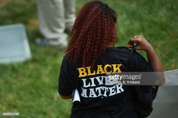 A woman wears a shirt with 'Black Lives Matter' during a memorial service for slain 18 yearold Michael Brown Jr on August 9 2015 at the Canfield...