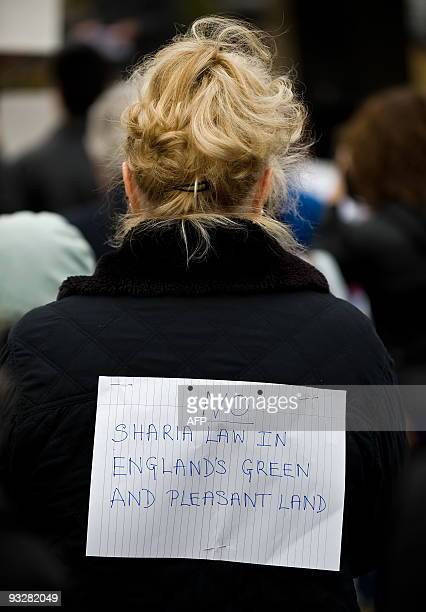 A woman wears a sign reading 'No Sharia Law in England's green and pleasant land' at an antiSharia law demonstration in Hyde Park central London on...