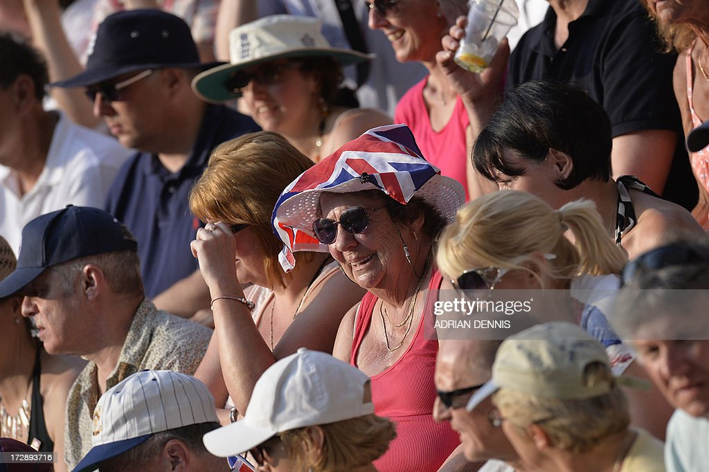A woman wears a small Union Flag on her head as she watches Anna Wintour watches Britain's Andy Murray play against Poland's Jerzy Janowicz in their men's singles semi-final match on day eleven of the 2013 Wimbledon Championships tennis tournament at the All England Club in Wimbledon, southwest London, on July 5, 2013.