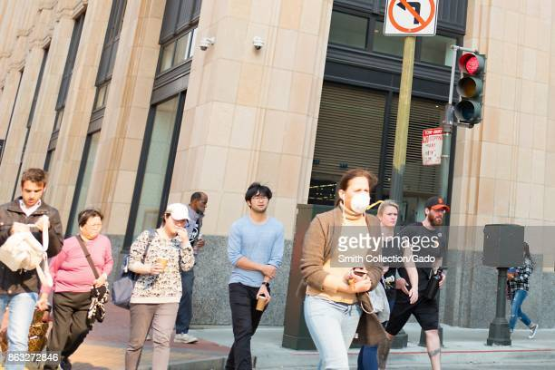 A woman wears a surgical face mask while crossing a street outside the headquarters of Twitter in the South of Market neighborhood of San Francisco...
