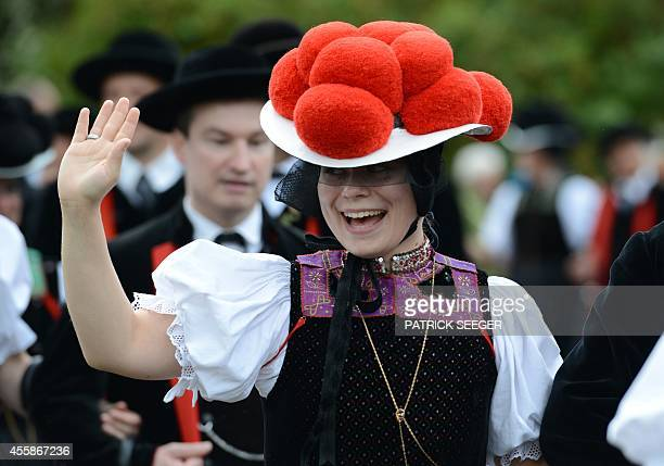 A woman wears a traditional Black Forest costume and a hat topped with pompoms a socalled Bollenhut during a pageant on the occasion of the 50th...