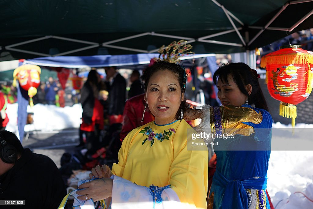 A woman wears a traditional Chinese dress as members of the Chinese American community, tourists and other New Yorkers celebrate the first day of the Lunar New Year, the Year of the Snake, in New York's Chinatown on February 10, 2013 in New York City. Celebrations are being held in Chinese communities around the world. The lighting of firecrackers are believed to ward off evil spirits and to bring the god of wealth into people's lives once New Year's Day arrives.