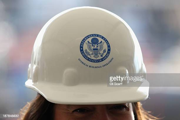 A woman wears a 'US Department of State for Overseas Building Operations' hard hat at the Groundbreaking Ceremony on the construction site for the...