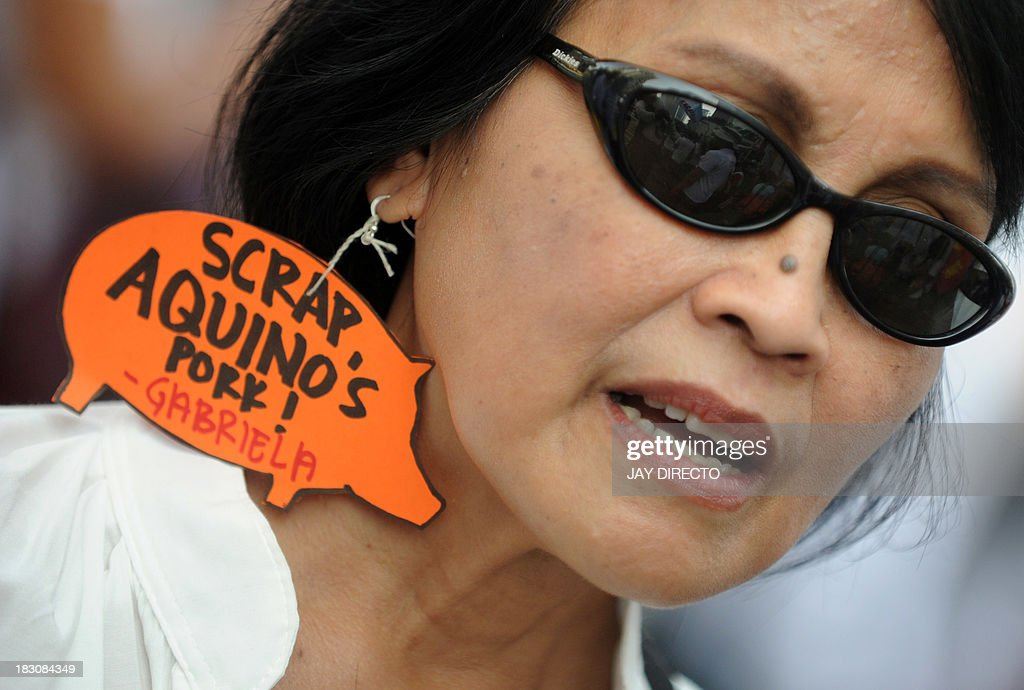 A woman wears an earing reading 'Scrap Aquino's Pork' hundreds of people march to a protest rally at the Philippine financial district in suburban Manila on October 4, 2013, carrying a huge golden pig to condemn politicians for their misuse of their 'pork barrel' funds, referring to money allocated to congressmen and other officials supposedly for their pet development projects but which often are siphoned away for corruption. This is the third such rally against the pork barrel issue organised partly through social media since August. But in this rally, there are more placards and banners condemning President Benigno Aquino for alleged tolerance of this corruption. AFP PHOTO / Jay DIRECTO