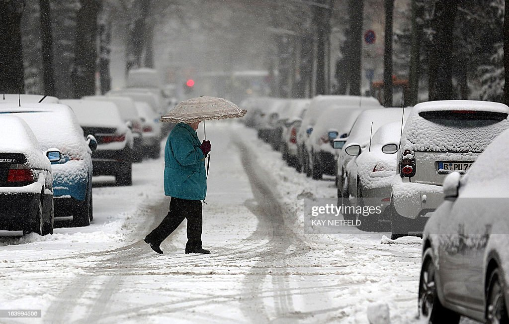 A woman wears an umbrella to protect from the snow as she crosses a snow-covered street during a snowfall in Berlin, on March 19, 2013. OUT +++
