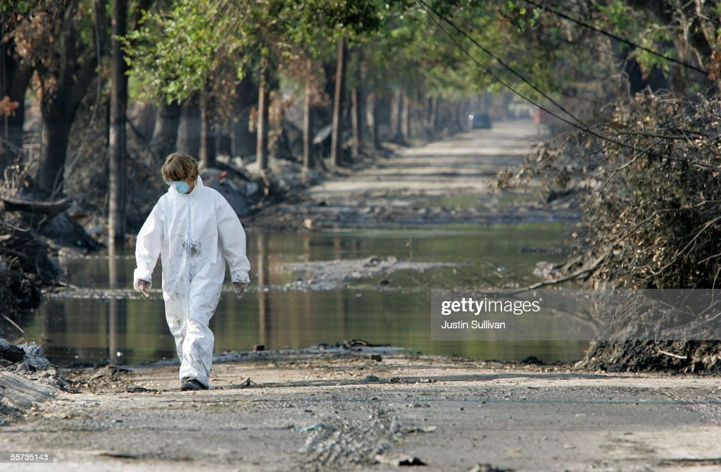 A woman wears protective clothing while walking down a street September 21, 2005 in the Lakefront district of New Orleans, Louisiana. Workers are rushing to repair breaches in levees in preparation of Hurricane Rita which could possibly hit the coast of Louisiana, just three weeks after Hurricane Katrina.
