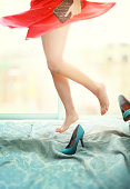 Woman wears red skirt jumping on the bed.