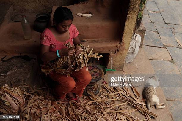 A woman weaves basket with dry palm leaves at her home in Bandipur village Nepal June 26 2010