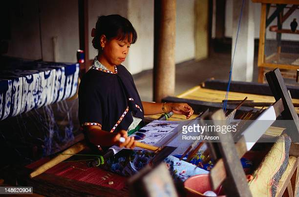 Woman weaving on traditional loom in workshop producing traditional Ikat and Songket woven fabrics.