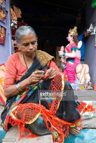 A woman weaving umbrella decorations at Bijapur, Karnataka, India