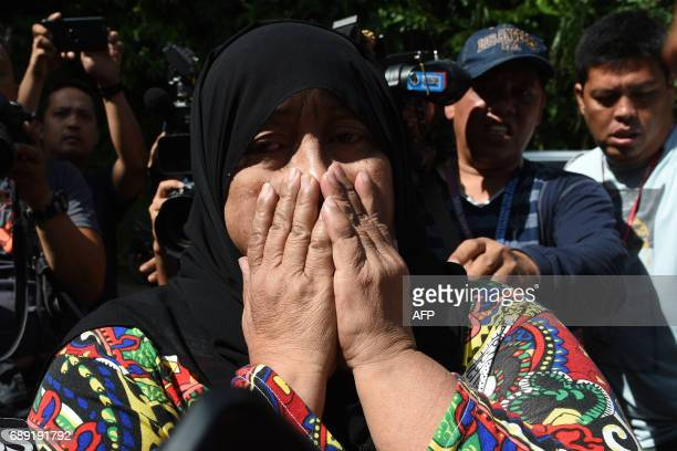A woman weeps after identifying bodies dumped off a cliff along the highway leading to Marawi in the southern island of Mindanao on May 28 2017...