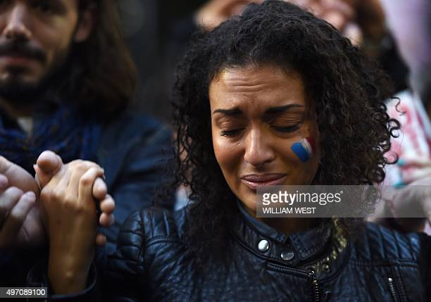 A woman weeps as she holds hands with others at a vigil held by the local French community in Sydney on November 14 as Australians express their...