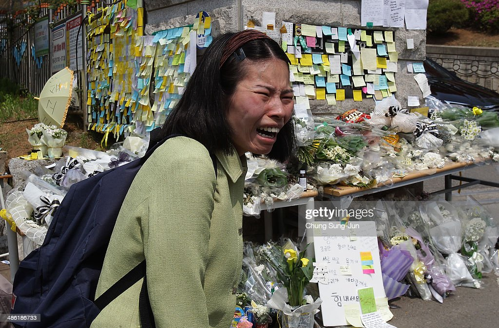 A woman weeps as she read messages wishing for the safe return of missing passengers of sunken passengers ship at Danwon high school on April 23, 2014 in Ansan, South Korea. At the altar, Friends and relatives are able to pay tribute to those who have passed in the April 16 ferry disaster off of Jindo Island in South Korea. The confirmed death toll now reached 150, and more than 150 people are still missing, as reported.