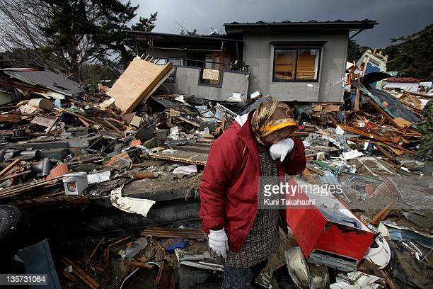 A woman weeps as she returns to check her house in Kadonowakicyo after massive earthquake and tsunami hit northern Japan on March 26 2011 in...