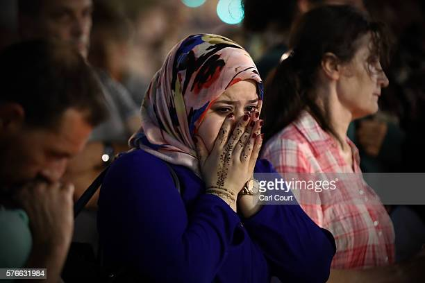 A woman weeps as she views flowers and tributes on the Promenade des Anglais on July 16 2016 in Nice France Five people believed to be linked to the...