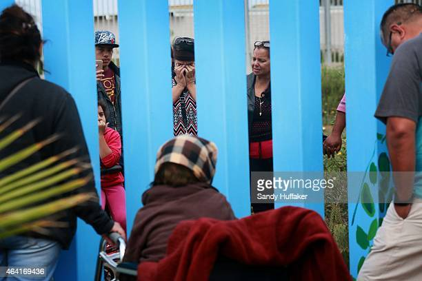 A woman weeps as she visits her family members through the border fence along the USMexico border on February 22 2015 in Tijuana Mexico Senior...