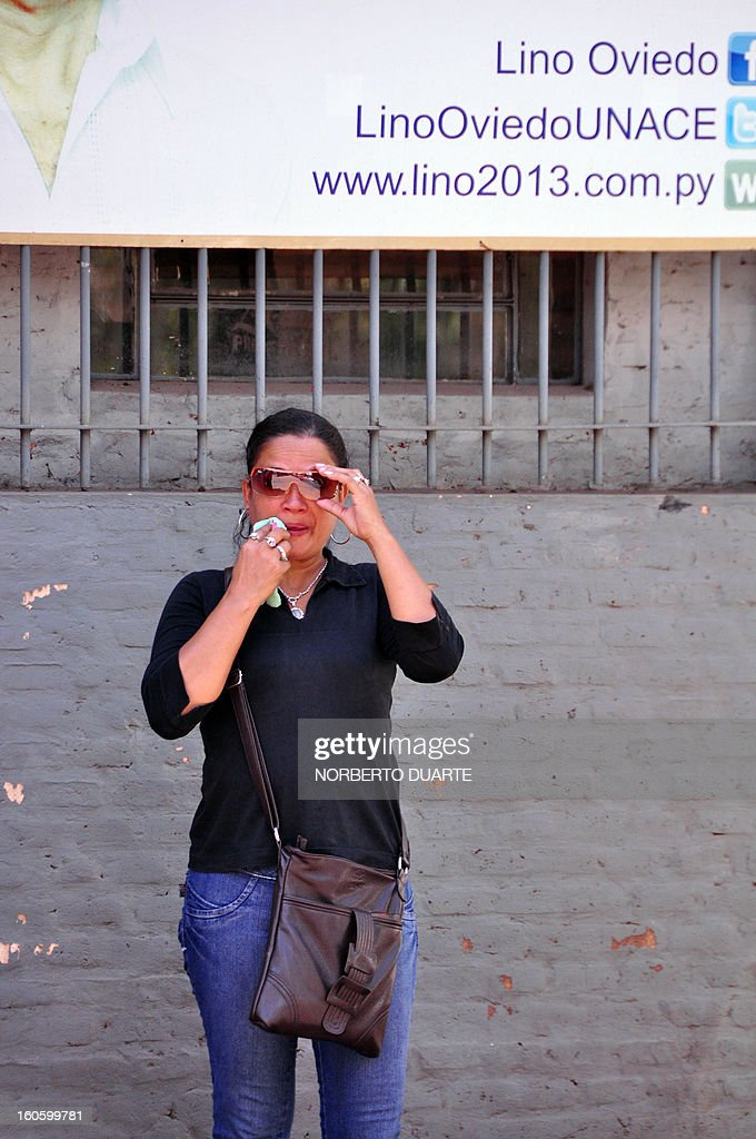 A woman weeps in front of a large prpaganda billboard of former Paraguayan general and presidential candidate for the UNACE party, Lino Oviedo, at the party's headquarters in Asuncion on February 3, 2013. Oviedo died on the eve in a helicopter crash whilst returning from a campaign rally in Concepcion. All three passengers of the aircraft --Ovideo, his bodyguard and the pilot-- died in the accident. AFP PHOTO Norberto Duarte