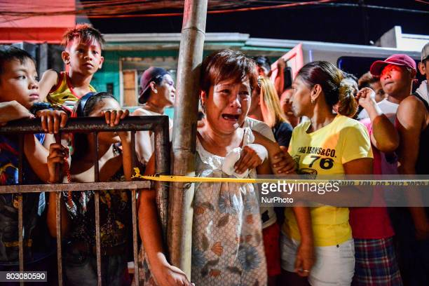 A woman weeps near the scene where a suspected drug user was shot dead by unknown assailants in Navotas north of Manila Philippines June 20 2017...