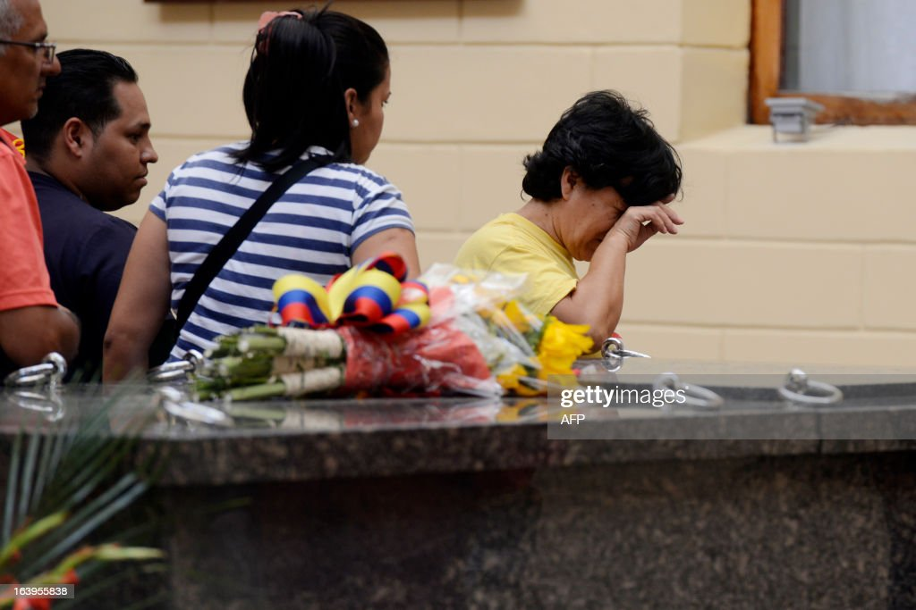 A woman weeps while visiting the remains of late Venezuelan President Hugo Chavez at the 'Quarter of the Mountain' in the 23 de Enero Chavez bastion, in Caracas, on March 18, 2013. The 'Quarter of the Mountain', where the body of Chavez lies, while deciding on its transfer to the National Pantheon, is a former barracks that was the center of operations of the failed coup led by Chavez on February 4, 1992. AFP PHOTO/LEO RAMIREZ