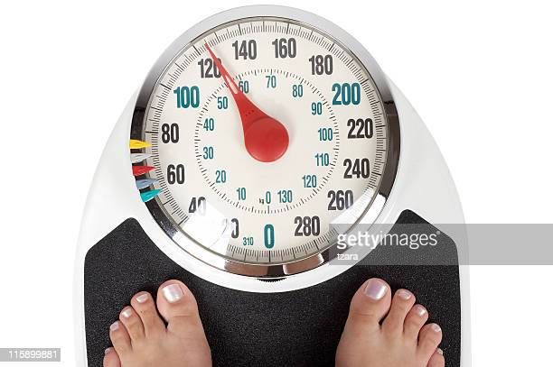 A woman weighing herself on bathroom scales