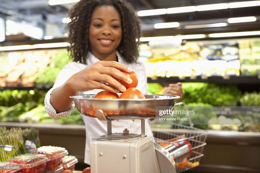 Woman weighing produce in supermarket : Stock Photo
