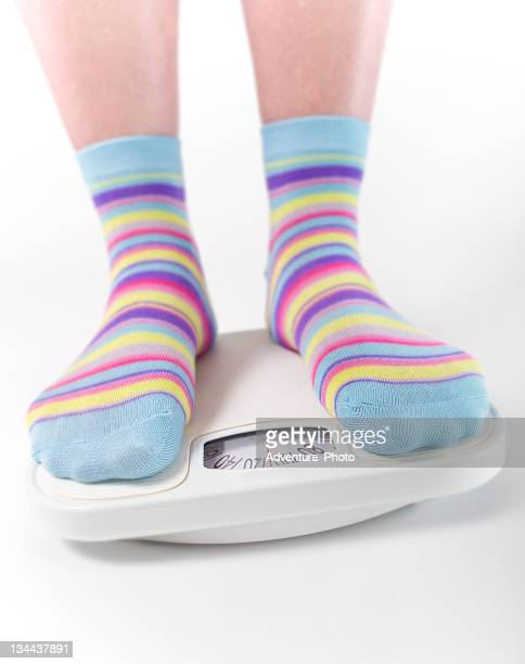 Woman Weighs Herself on Scale with Colorful Socks