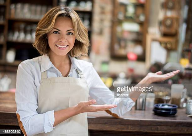 Woman welcoming people to the coffee shop