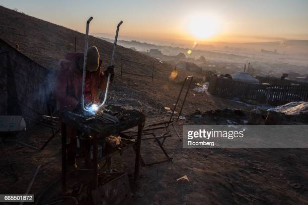 A woman welds at a table in a ger district in Ulaanbaatar Mongolia on Tuesday March 14 2017 The subzero winters in Ulaanbaatar force residents burn...
