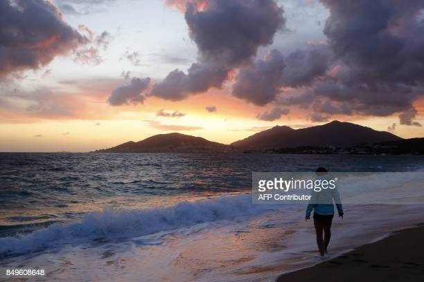 A woman wets her feet at the Ricanto beach at sunset as Ajaccio is seen in the background on September 19 2017 on the French Mediterranean Island of...