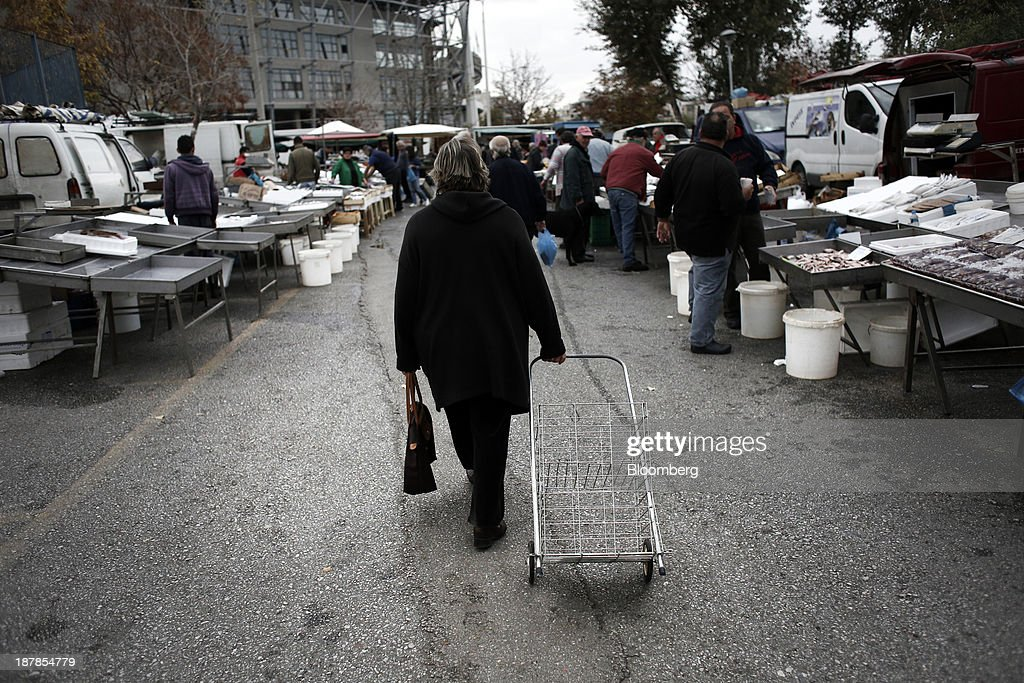 A woman wheels her empty shopping trolley past fresh fish stalls at a farmer's market in the Toumpa district of Thessaloniki, Greece, on Wednesday, Nov. 13, 2013. Greece 'is following a fiscal adjustment program that aims to make the country's public finances sustainable on a permanent basis,' Finance Minister Yannis Stournaras told lawmakers during the debate, after holding talks with the troika earlier in the week. Photographer: Konstantinos Tsakalidis/Bloomberg via Getty Images