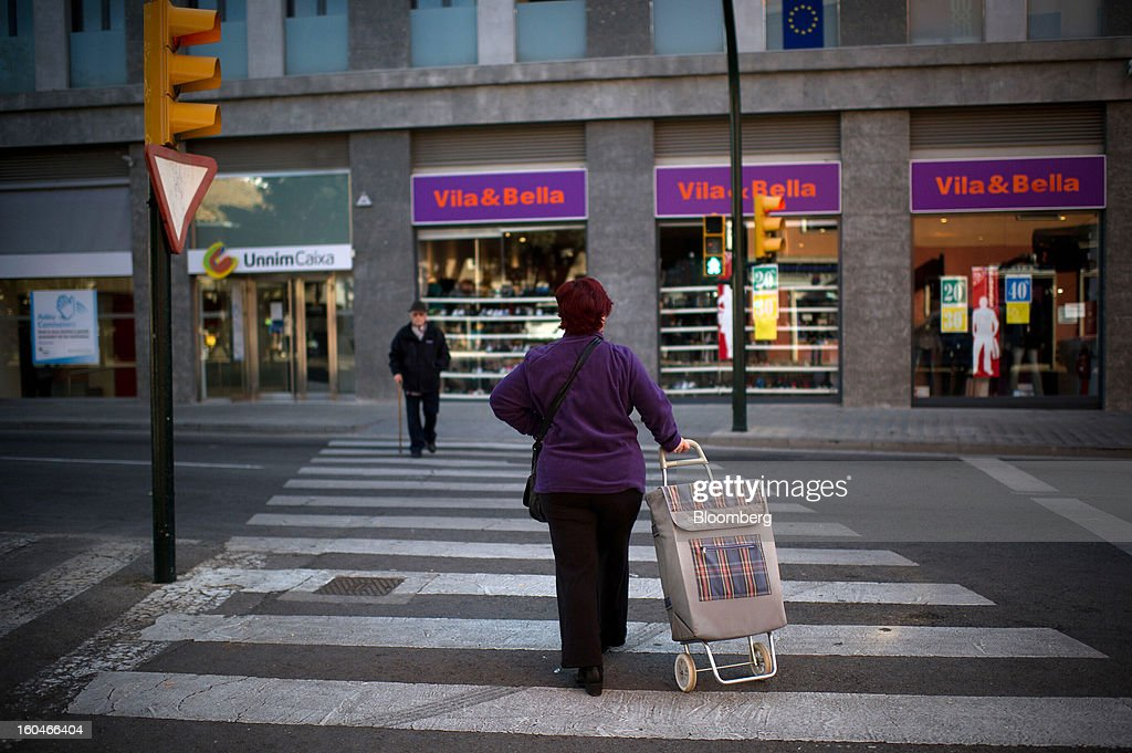 A woman wheels her shopping cart across a pedestrian crossing in Figueres, Spain, on Thursday, Jan. 31, 2013. Spain's recession deepened more than economists forecast in the fourth quarter as the government's struggle to rein in the euro region's second-largest budget deficit weighed on domestic demand. Photographer: David Ramos/Bloomberg via Getty Images