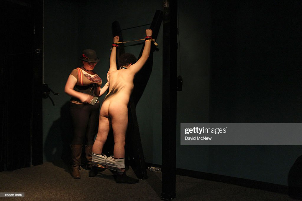 A woman whips a voluntarily submissive man tied who is up at a dungeon party during the domination convention, DomCon LA, in the early morning hours of May 11, 2013 in Los Angeles, California. The annual convention was started in 2003 by fetish professional Mistress Cyan to bring together enthusiasts of BDSM (Bondage, Discipline, Submission and Dominance) and other fetishes.