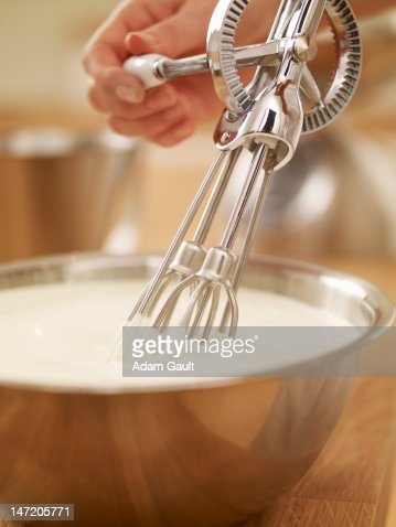 Woman whisking cream with egg beater
