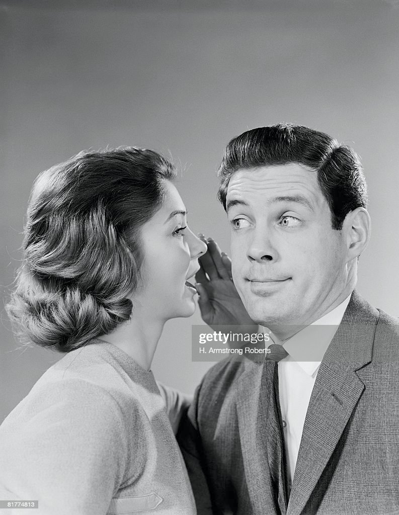 Woman whispering into man's ear, man pulling funny face. : Stock Photo