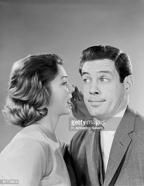 Woman whispering into man's ear, man pulling funny face.