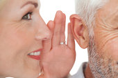 Close up of a woman whispering secret into a mans ear over white background