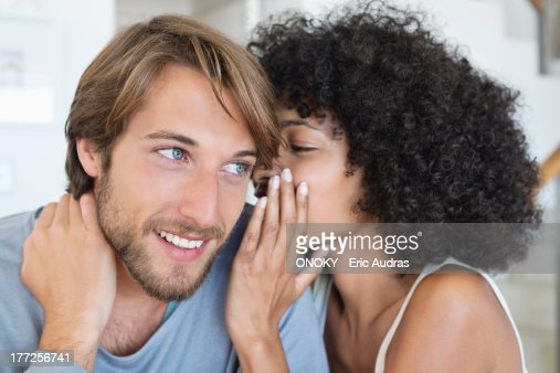 Woman whispering to a man : Stock Photo