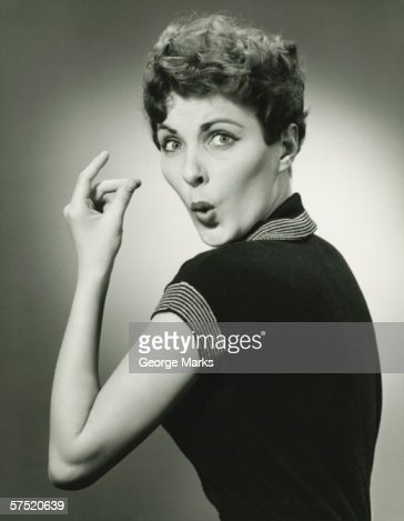 Woman whistling and snapping fingers in studio, (B&W), portrait