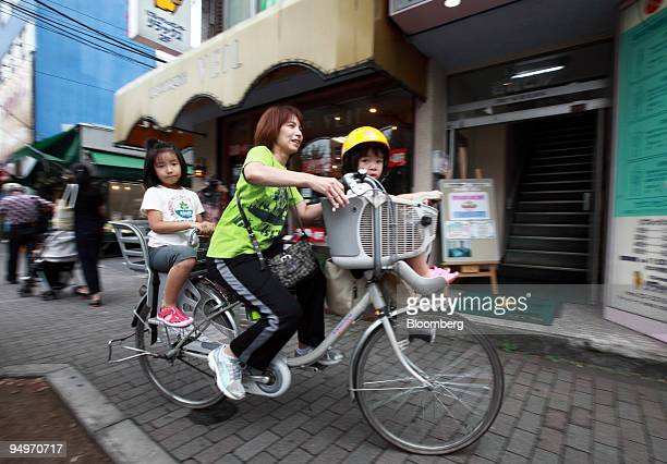 A woman who declined to be identified pedals a batterypowered bicycle with her children in Tokyo Japan on Friday July 31 2009 Domestic sales of...