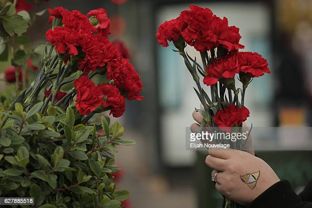 A woman who declined to be identified places carnations on a hedge near the site of a warehouse fire that has claimed the lives of at least thirtysix...