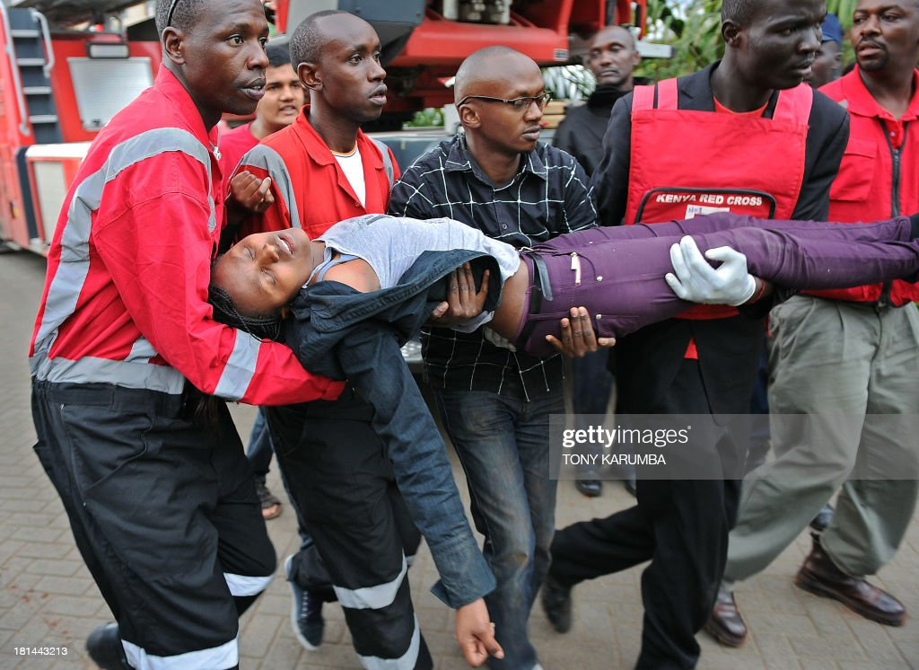 A woman who had been held hostage is carried in shock by rescue personnel on September 21, 2013, after she was freed following a security operation at an upmarket shopping mall in Nairobi where suspected terrorrists engaged Kenyan security forces in a drawn out gun fight. Some 20 people have been killed and about 50 wounded Saturday in the initial attack by the gunmen the Kenya Red Cross said. AFP PHOTO / Tony KARUMBA