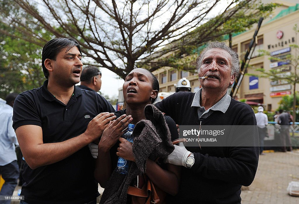 A woman (C) who had been held hostage reacts in shock on September 21, 2013 after she was freed following a security operation at an upmarket shopping mall in Nairobi where suspected terrorrists engaged Kenyan security forces in a drawn out gun fight. Some 20 people have been killed and about 50 wounded Saturday in the initial attack by the gunmen the Kenya Red Cross said. AFP PHOTO / Tony KARUMBA