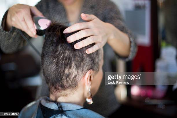 A woman who has her head shaved by a hairdresser