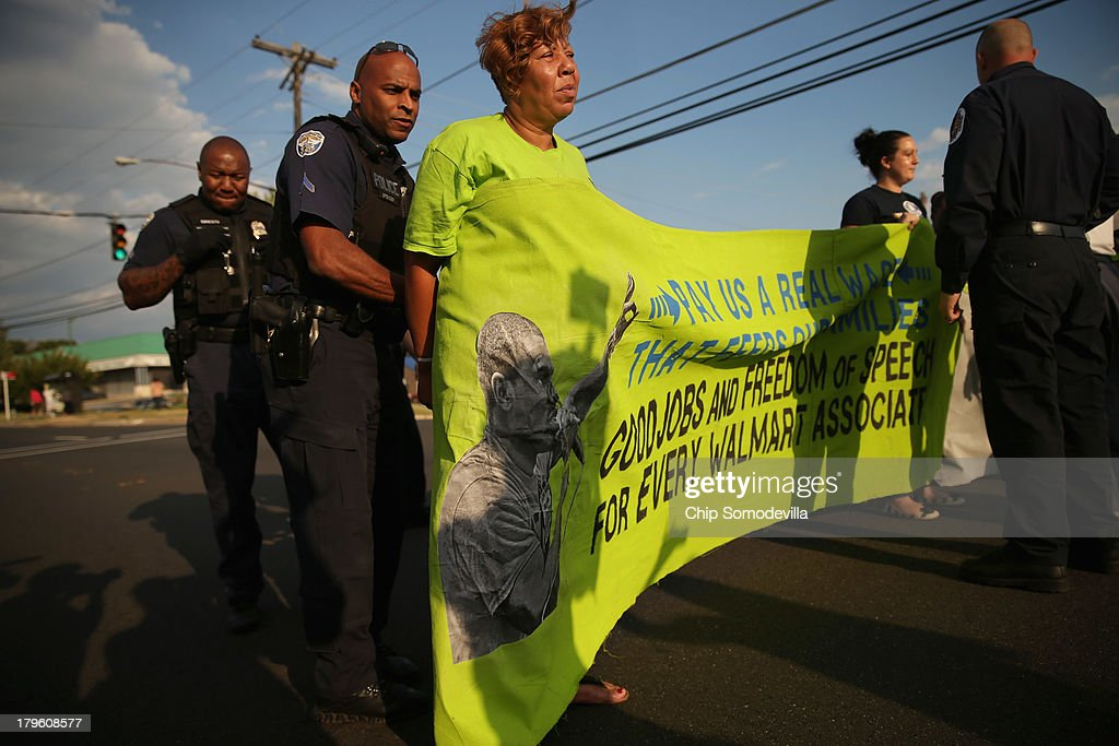 A woman who identified herself only as Tonya C and says she was fired from a Walmart store, is arrested after she and hundreds of other demonstrators blocked traffic in a major intersection outside a Walmart store during rush hour September 5, 2013 in Hyattsville, Maryland. About 225 people gathered outside the Walmart store to protest the retail giant's labor practices. A showdown continues between Walmart and the neighboring District of Columbia, where Mayor Vincent Gray could sign a bill that would make large retailers to pay their employees a 50 percent premium over the city's minimum wage.