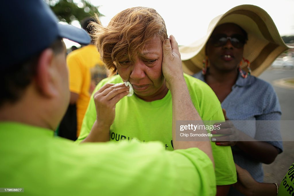 A woman who identified herself only as Tonya C, and says she was fired from a Walmart store, is comforted by friends during a pro-labor rally and demonstration outside a Walmart store September 5, 2013 in Hyattsville, Maryland. About 225 people gathered outside the Walmart store to protest the retail giant's labor practices A showdown continues between Walmart and the neighboring District of Columbia, where Mayor Vincent Gray could sign a bill that would make large retailers to pay their employees a 50 percent premium over the city's minimum wage.