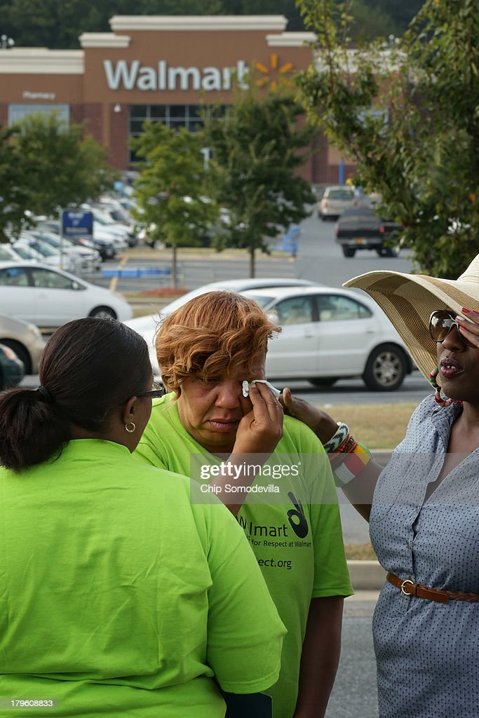 A woman who identified herself only as Tonya C, and says she was fired from a Walmart store, is comforted by friends during a demonstration outside a Walmart store September 5, 2013 in Hyattsville, Maryland. About 225 people gathered outside the Walmart store to protest the retail giant's labor practices A showdown continues between Walmart and the neighboring District of Columbia, where Mayor Vincent Gray could sign a bill that would make large retailers to pay their employees a 50 percent premium over the city's minimum wage.