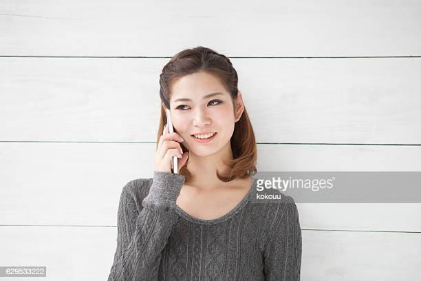 Woman who is calling on a smartphone while laughing