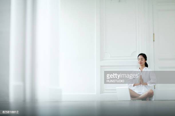 woman who is closing her eyes and playing yoga pose in the house