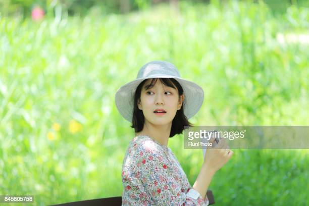 woman who is holding a cup of coffee in a park and looking back