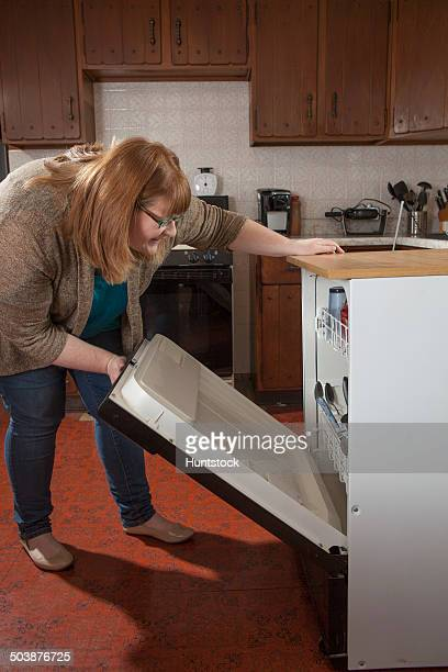 Woman who is legally blind loading the dishwasher in her kitchen